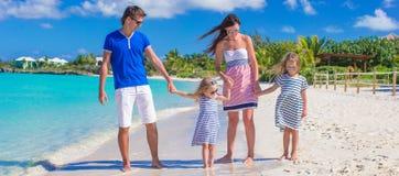 Familia joven con dos niños en la playa blanca tropical Imagen de archivo libre de regalías