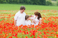 Familia joven con dos niños - hijo e hija recién nacida - que presentan en campo de flor de la amapola Fotos de archivo libres de regalías
