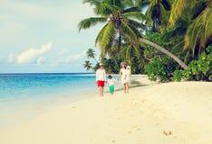 Familia joven con dos niños que caminan en la playa tropical Fotografía de archivo libre de regalías