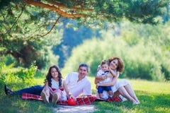 Familia joven con dos niños que se sientan en la hierba debajo de un árbol de pino foto de archivo