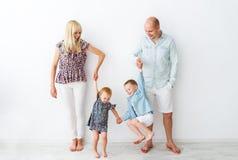 Familia joven con dos niños que se unen Imagen de archivo libre de regalías