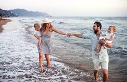 Familia joven con dos ni?os del ni?o que caminan en la playa el vacaciones de verano fotos de archivo libres de regalías