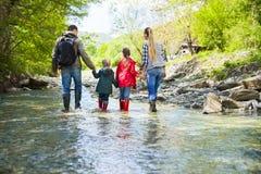 Familia joven con dos pequeñas hijas en viaje de la montaña foto de archivo