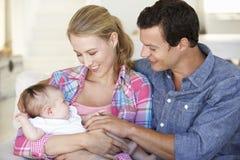 Familia joven con el bebé que se relaja en Sofa At Home fotos de archivo libres de regalías
