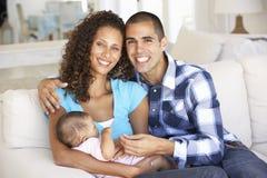 Familia joven con el bebé que se relaja en Sofa At Home Foto de archivo