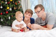Familia joven con el bebé y las decoraciones de la Navidad Fotos de archivo
