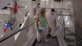 Familia joven con la escalera móvil del montar a caballo del niño en centro comercial almacen de metraje de vídeo
