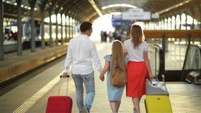Familia joven con la hija linda, caminando en la maleta ferroviaria de la tenencia de la plataforma El mejor concepto del viaje y metrajes