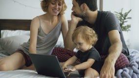 Familia joven con la niña linda que juega con la hija mientras que ella que mecanografía en el ordenador portátil que se sienta e almacen de video