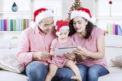 Familia joven con la tableta en el tiempo de la Navidad Fotos de archivo libres de regalías