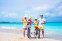 Familia joven con las bicis del paseo de los niños encendido Imagen de archivo libre de regalías