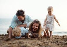 Familia joven con los niños del niño que juegan con la arena en la playa el vacaciones de verano imagenes de archivo