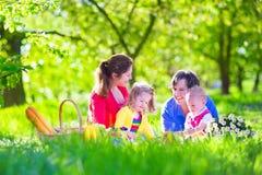 Familia joven con los niños que tienen comida campestre al aire libre Imagenes de archivo
