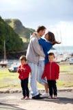 Familia joven con los pequeños niños en un puerto por la tarde Imagenes de archivo