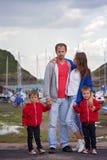 Familia joven con los pequeños niños en un puerto por la tarde Fotos de archivo libres de regalías