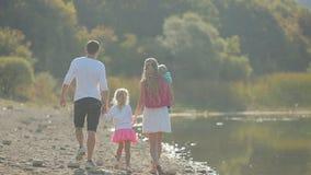 Familia joven con los pequeños niños que caminan a lo largo de