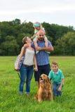 Familia joven con su perro casero, golden retriever Imagen de archivo libre de regalías