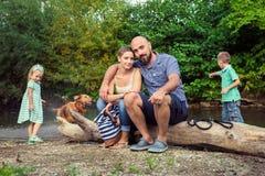 Familia joven con su perro casero, golden retriever Fotografía de archivo libre de regalías