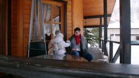 Familia joven con un pequeño bebé que bebe bebidas calientes en el mirador de una casa hermosa almacen de metraje de vídeo