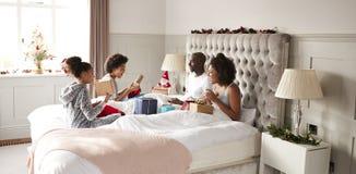 Familia joven de la raza mixta que se sienta en los regalos de apertura de la cama en dormitorio del ½ del ¿del parentsï el mañan fotos de archivo