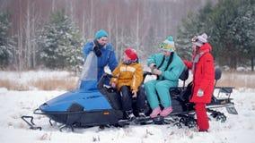 Familia joven del bosque del invierno en la ropa colorida que descansa para arriba por la moto de nieve Bebidas calientes de cons almacen de metraje de vídeo