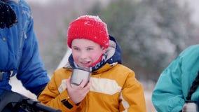 Familia joven del bosque del invierno en la ropa colorida que descansa para arriba por la moto de nieve Pasando en un círculo una almacen de video