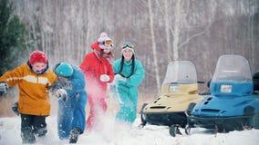 Familia joven del bosque del invierno en la ropa colorida que juega bolas de nieve cerca de las motos de nieve funcionamiento a l almacen de metraje de vídeo