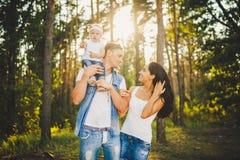 Familia joven elegante de blonde de un año de la mamá, del papá y de la hija que se sienta cerca de padre en hombros, al aire lib Imagen de archivo libre de regalías