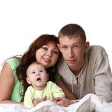 Familia joven en cama: bebé, hombre, mujer Imagen de archivo libre de regalías