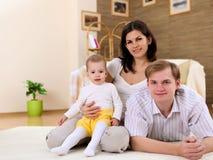 Familia joven en casa que juega con un bebé fotografía de archivo