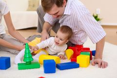 Familia joven en casa que juega con un bebé imagenes de archivo