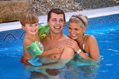 Familia joven en la piscina imagen de archivo