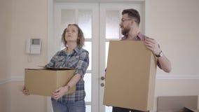 Familia joven en ropa informal con las cajas en las manos que se colocan en sitio semivacío y que miran alrededor de cierre para  almacen de metraje de vídeo