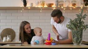 Familia joven feliz con el bebé recién nacido Madre, padre y bebé recién nacido Mamá feliz y papá que besan y que abrazan al niño almacen de video