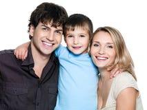 Familia joven feliz con el hijo sonriente Imagenes de archivo