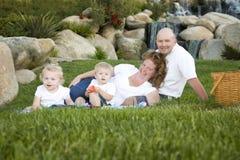 Familia joven feliz con el retrato de los gemelos en parque Imagenes de archivo