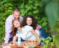 Familia joven feliz con la hija en comida campestre Fotos de archivo