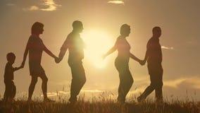 Familia joven feliz con los niños que corren alrededor del campo, silueta en la puesta del sol almacen de video