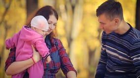 Familia joven feliz con recién nacido en parque del otoño metrajes