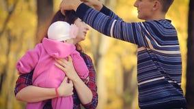 Familia joven feliz con recién nacido en parque del otoño almacen de metraje de vídeo