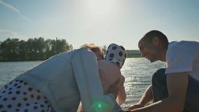 Familia joven feliz con una pequeña hija en la arena que disfruta junto de puesta del sol en la orilla del lago de la ciudad Vera almacen de metraje de vídeo