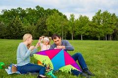 Familia joven feliz con volar una cometa en el parque foto de archivo