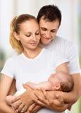 Familia joven feliz de madre, de padre y de bebé recién nacido en su a Foto de archivo libre de regalías