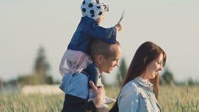 Familia joven feliz de tres personas junto en un campo del trigo entre las espiguillas verdes Una pequeña hija se sienta en metrajes