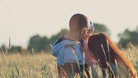 Familia joven feliz de tres personas junto en un campo del trigo entre las espiguillas verdes Una pequeña hija se sienta en almacen de video