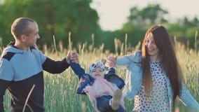 Familia joven feliz de tres personas junto en un campo de trigo entre las espiguillas verdes Los padres detienen a una pequeña hi almacen de metraje de vídeo