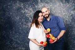 Familia joven feliz del vegano la muchacha embarazada y el hombre barbudo están sosteniendo manzanas en sus manos y sonrisa imagen de archivo libre de regalías