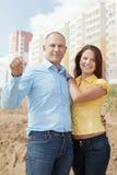 Familia joven feliz delante del nuevo hogar Fotos de archivo libres de regalías