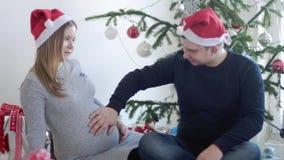 Familia joven feliz El marido lo abraza esposa embarazada para tocar su vientre cerca del árbol de navidad adornado hermoso Cámar
