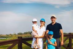 Familia joven feliz en club de campo del golf Foto de archivo